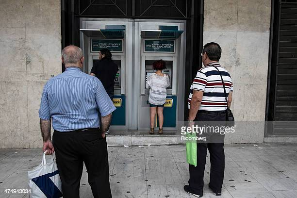 Customers queue to use automated teller machines outside a National Bank of Greece SA bank branch in Thessaloniki Greece on Wednesday May 27 2015...