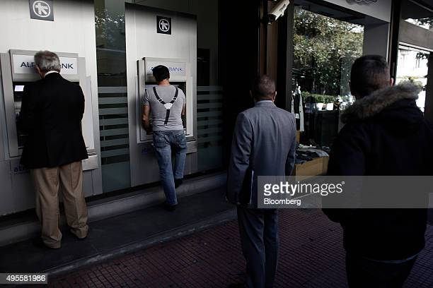 Customers queue to use automated teller machines outside an Alpha Bank AE bank branch in Athens Greece on Tuesday Nov 3 2015 Greece's four biggest...
