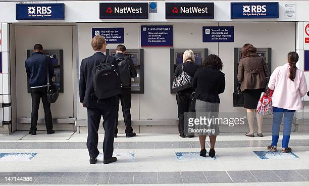 Customers queue to use Royal Bank of Scotland Group Plc and NatWest automated teller machines on the concourse at Liverpool Street rail station in...