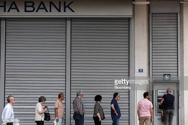 Customers queue to withdraw cash from an automated teller machine outside a closed branch of the Alpha Bank AE in Athens Greece on Tuesday June 30...