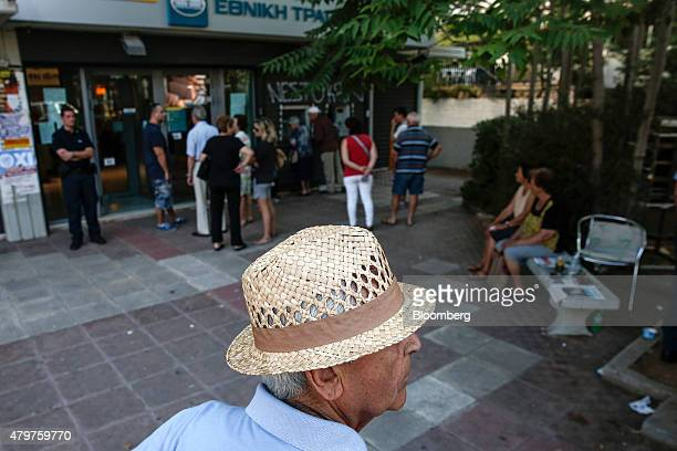 Customers queue to withdraw cash from an automated teller machine outside a National Bank of Greece SA bank branch in Athens Greece on Tuesday July 7...