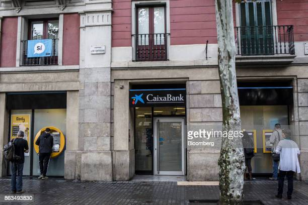 Customers queue to withdraw cash from an automated teller machine outside a CaixaBank SA bank branch in Barcelona Spain on Friday Oct 20 2017 In a...