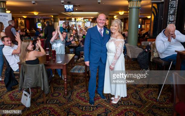 Customers react as newly weds Stuart and Diana Greenwood celebrate their wedding day at the Regal Moon JD Wetherspoons pub on July 04, 2020 in...