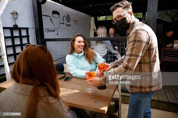 Customers react as their drinks are delivered to their outside table at a re-opened pub in east London as coronavirus restrictions are eased across...