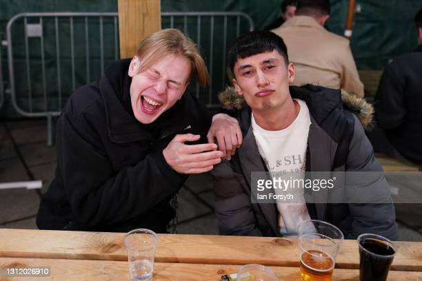 Customers react as they enjoy a drink at the Switch bar in Newcastle shortly after midnight following the easing of lockdown measures on April 12,...