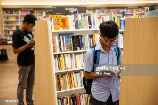 Customers read books in the Kinokuniya Co book store at the Aeon Mall in Phnom Penh Cambodia Sunday May 26 2019 Kinokuniya Japan's largest bookstore...
