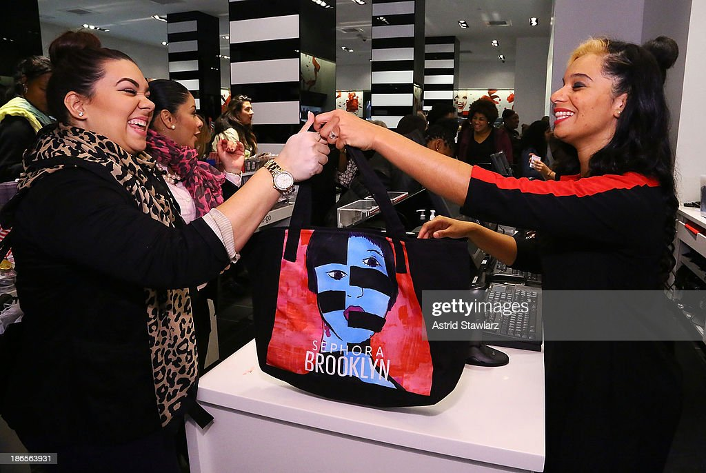 Customers receive a Sephora Brooklyn tote bag featuring artwork by illustrator Gary Panter at Sephora Brooklyn Grand Opening on November 1, 2013 in New York City.