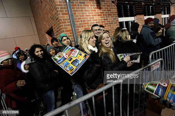 Customers receive WalMart sales circulars as they wait in line to enter the store Thanksgiving day on November 28 2013 in Troy Michigan Black Friday...