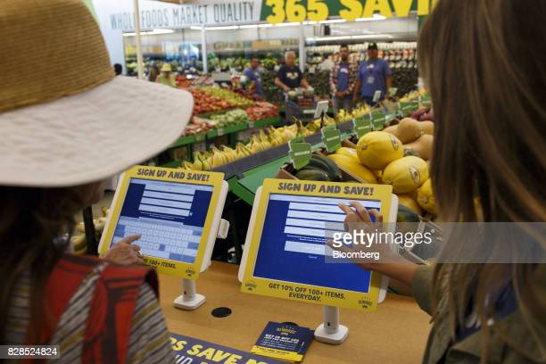 Customers register for the 365 Rewards discount program during the grand opening of a Whole Foods Market 365 location in Santa Monica California US...