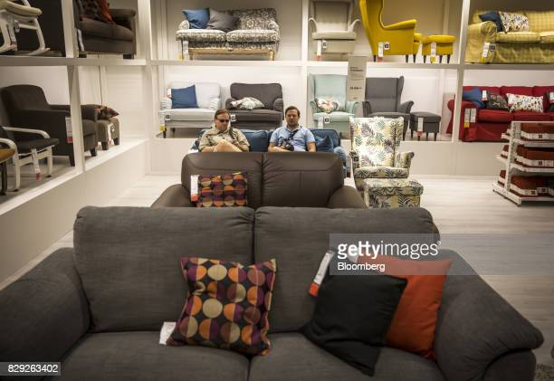 Customers rest on a sofa in the home seating department while shopping on the opening day of IKEA of Sweden AB's first department store in Belgrade...