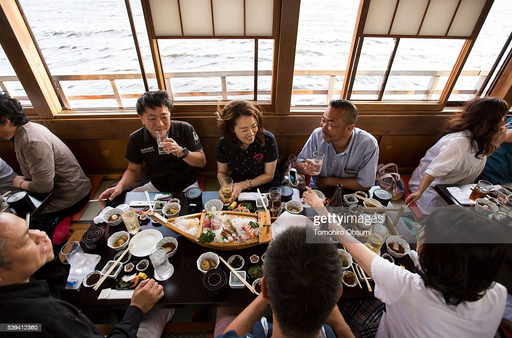 Customers ride on a yakatabune, or traditional low barge style boat, operated by Mikawaya shipping agent, as it sails through Tokyo Bay on June 11, 2016 in Tokyo, Japan. About 35 companies operate over 100 yakatabune boats in Tokyo offering services such as dinner or karaoke inside the boats while cruising in Tokyo's bay area, according to the Tokyo Yakatabune Association.