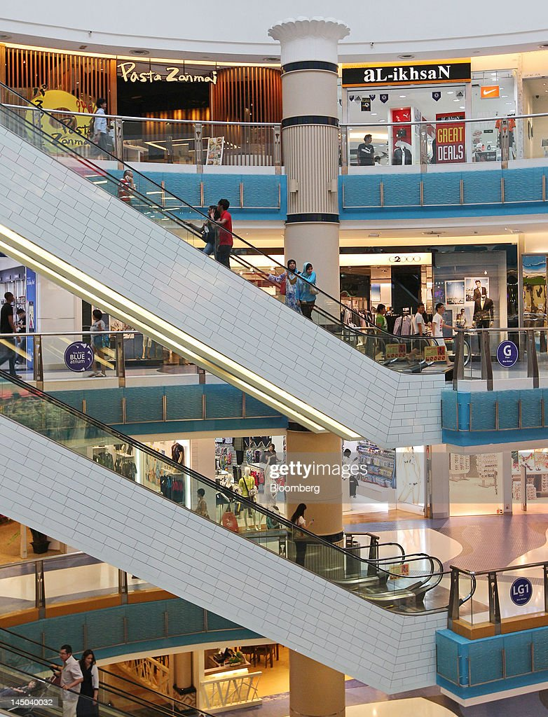 Customers ride on escalators in the Sunway Pyramid Shopping