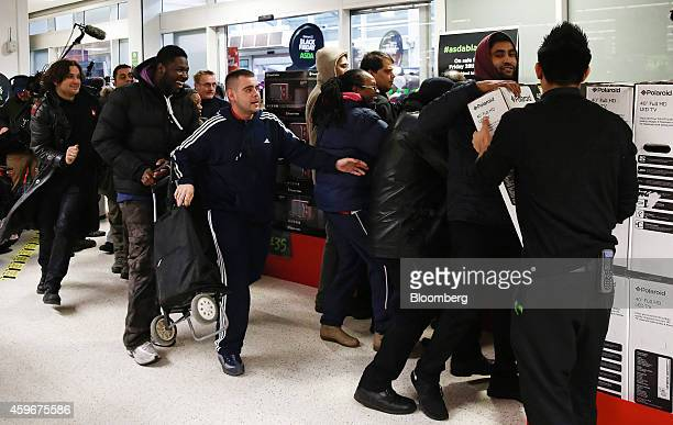 Customers rush to get to a sales display of reduced LED television sets during a Black Friday discount sale at an Asda supermarket operated by...