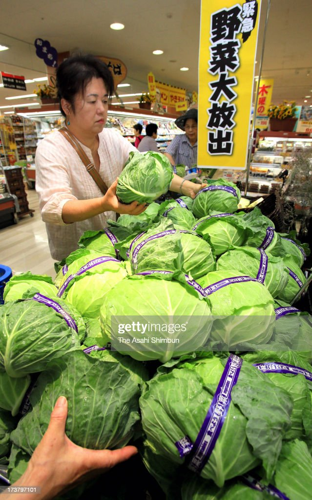Customers rush to stalls of vegetables sales at supermarket 'Daiei' Urayasu branch on July 18, 2013 in Urayasu, Chiba, Japan. Short rainy season and subsequent strong summer heat affect growth of vegetables such as lettuce, green peper, cucumber amd tomato.
