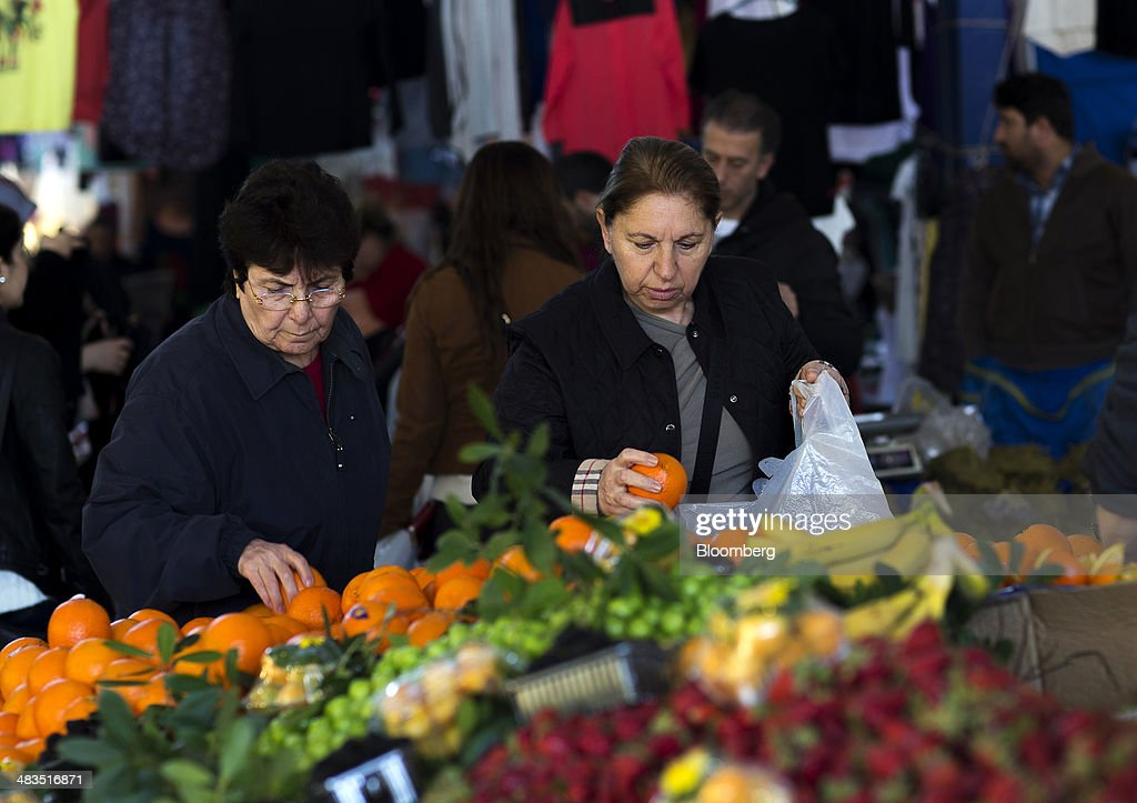 Customers select oranges for sale at a stall in the Yesilkoy street market in Istanbul, Turkey, on Wednesday, April 9, 2014. Turkish central bank Governor Erdem Basci indicated to analysts in London on April 3 that he planned to keep monetary policy tight to control inflation. Photographer: Kerim Okten/Bloomberg via Getty Images