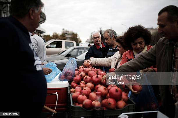 Customers select pomegranates from a stall at a farmers' market in Thessaloniki Greece on Saturday Nov 16 2013 Greek Prime Minister Antonis Samaras...