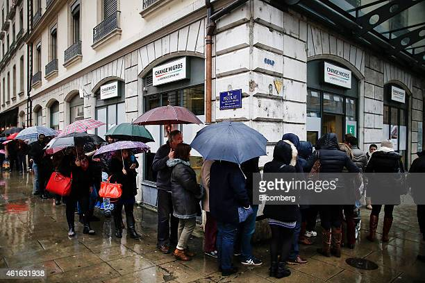 Customers shelter under umbrellas from the rain as they queue around the block to exchange their currency after the Swiss central bank ended the cap...