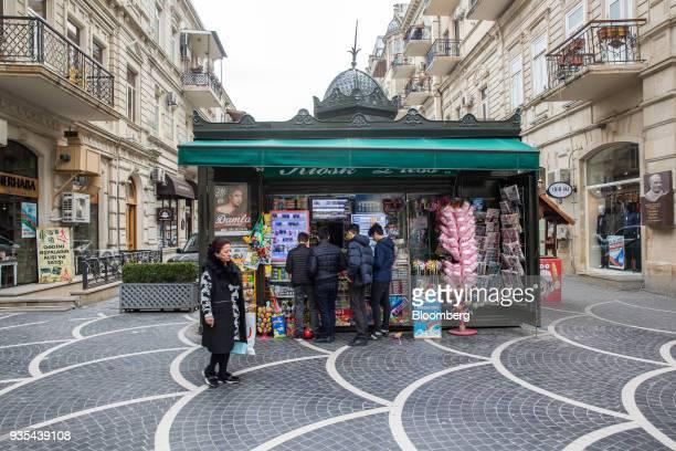 Customers shop at a kiosk in Baku Azerbaijan on Friday March 16 2018 Azerbaijan's economy barely returned to growth last year increasing 01 percent...