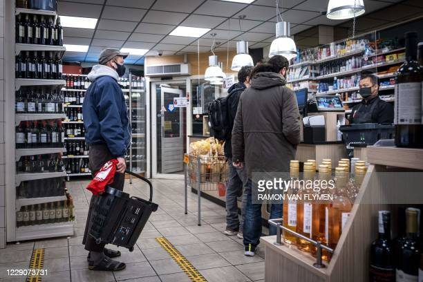 Customers shop at a night grocery store in Amsterdam on October 14 2020 The Netherlands will go into partial lockdown to curb one of Europe's biggest...