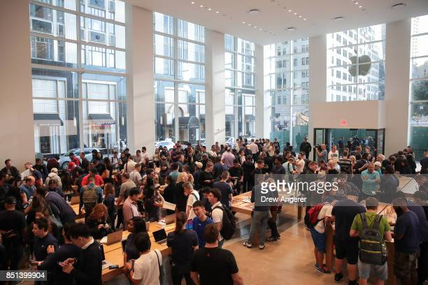 Customers shop at the Fifth Avenue Apple Store September 22 2017 in New York City The new iPhone 8 and iPhone 8 Plus as well as the updated Apple...