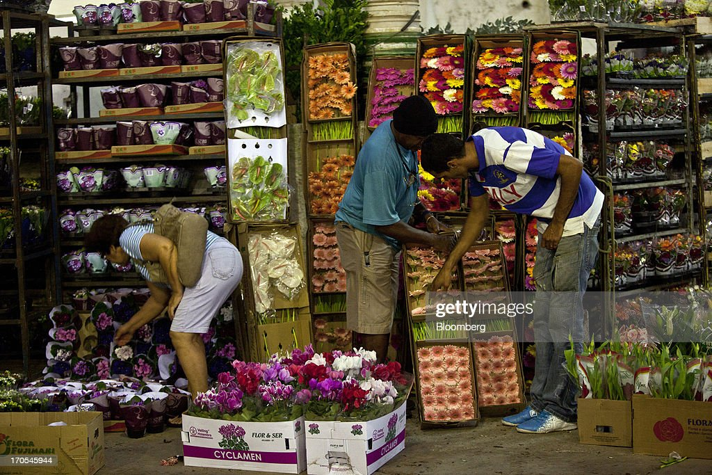 Customers shop for flowers at a market in Rio de Janeiro, Brazil, on Thursday, June 13, 2013. Brazilian retail sales rose in April at less than half the pace economists forecast as inflation erodes purchasing power, complicating the governments effort to boost growth. Photographer: Dado Galdieri/Bloomberg via Getty Images