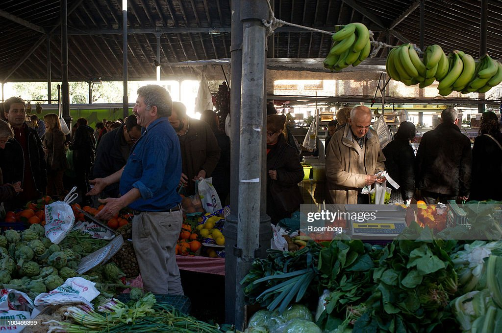 Customers shop for fresh fruit and vegetables at the weekly market in Figueres, Spain, on Thursday, Jan. 31, 2013. Spain's recession deepened more than economists forecast in the fourth quarter as the government's struggle to rein in the euro region's second-largest budget deficit weighed on domestic demand. Photographer: David Ramos/Bloomberg via Getty Images