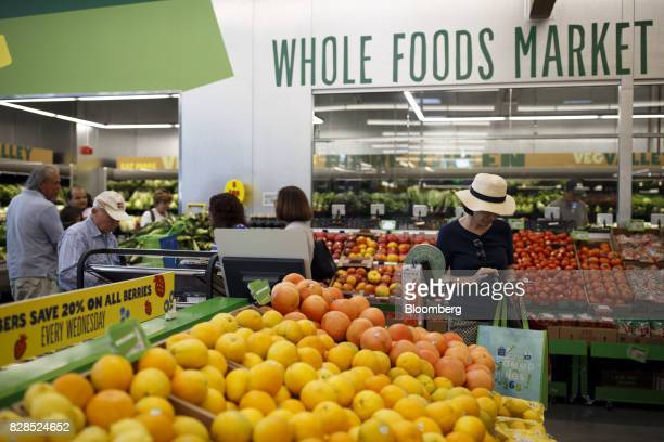 Customers shop for produce during the grand opening of a Whole Foods Market 365 location in Santa Monica California US on Wednesday Aug 9 2017 The...