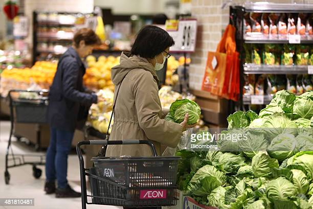 Customers shop for vegetables at an Aeon Co supermarket in Chiba Japan on Tuesday April 1 2014 Japan's economy will probably withstand a sales tax...