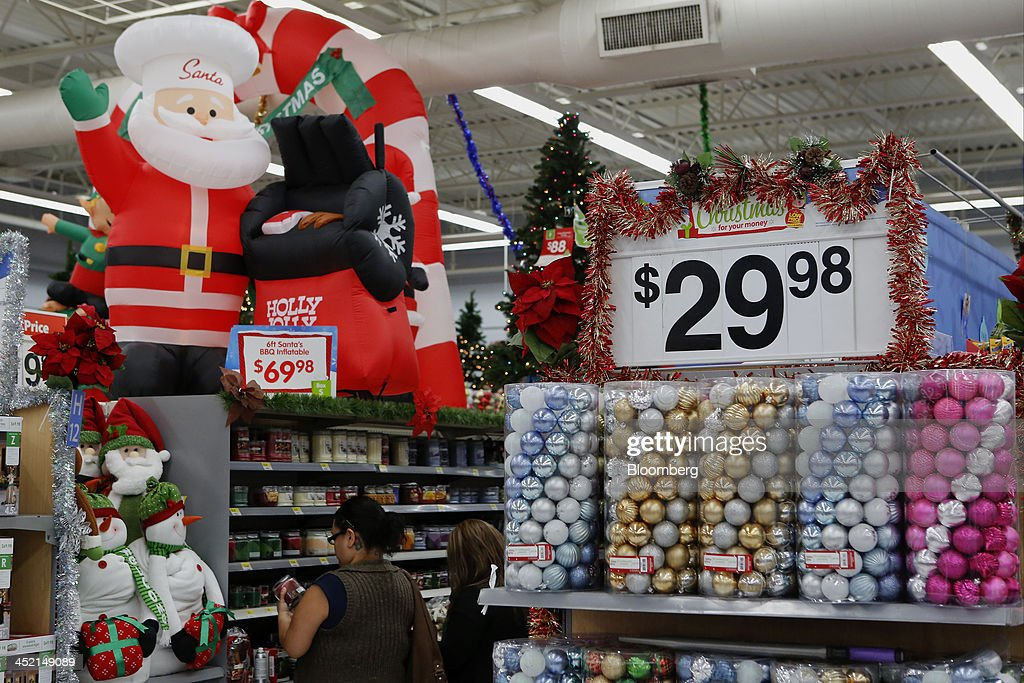 Customers shop holiday decorations for sale at a Wal-Mart Stores Inc. location ahead of Black Friday in Los Angeles, California, U.S., on Tuesday, Nov. 26, 2013. Wal-Mart Stores Inc. said Doug McMillon, head of its international business, will replace Mike Duke as chief executive officer when he retires as the world's largest retailer struggles to ignite growth at home and abroad. Photographer: Patrick T. Fallon/Bloomberg via Getty Images