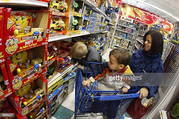 Customers shop in the toy truck department of a Toys R Us store January 28 2002 in Niles IL Toys R Us Inc plans to cut 1900 jobs and to close 27 Toys...