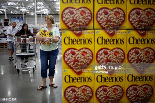 Customers shop near a display of General Mills Cheerios cereal at a Costco Wholesale Corp store in Louisville Kentucky US on Thursday May 29 2014...