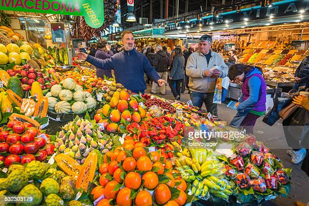 Customers shopping at colourful market stall La Boqueria Barcelona Spain