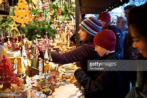 Customers shopping for Christmas ornaments at Christmas market Winter Wonderland in Hyde Park London