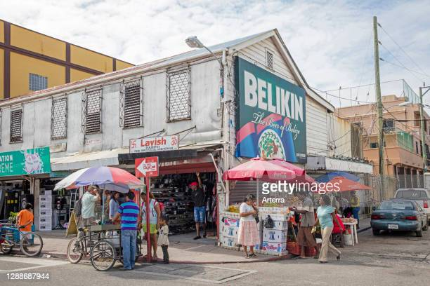 Customers shopping in busy street with shops and market stalls selling fruit in Belize City, Caribbean, Central America.