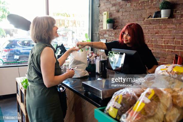 customers shopping in small zero waste oriented fruit and grocery store. - local produce stock pictures, royalty-free photos & images