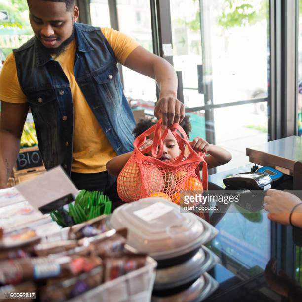 Customers shopping in small zero waste oriented fruit and grocery store.