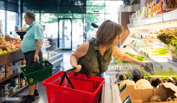 """小さなゼロ廃棄物指向の果物や食料品店で買い物をする顧客。 - """"martine doucet"""" or martinedoucet ストックフォトと画像"""