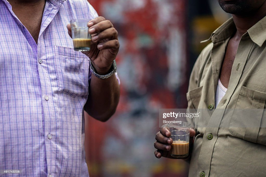 Customers sip glasses of chai at a roadside stall in Mumbai, India, on Friday, Sept. 25, 2015. Chai, the sweet, milky tea concoction popular in most of South Asia, is getting an image makeover in India. Rising incomes and demand for a refined tea experience transcending chai are spawning posh tea lounges in the nation's biggest cities. Photographer: Dhiraj Singh/Bloomberg via Getty Images