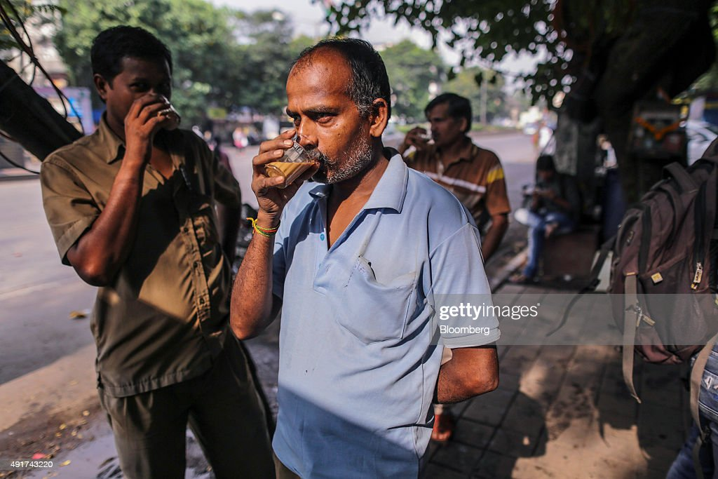 Customers sip glasses of chai at a roadside stall in Mumbai, India, on Friday, Sept. 25, 2015. That sweet and milky tea concoction called chai is getting an image makeover in India. Rising incomes and demand for a refined experience transcending chai are spawning posh tea lounges in the nation's biggest cities. Photographer: Dhiraj Singh/Bloomberg via Getty Images
