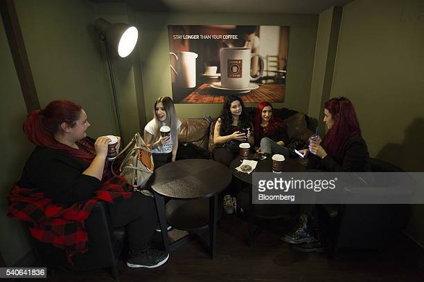 Customers sit and drink coffee in a branch of Arnold Coffee operated by American Coffee Company SpA in Milan Italy on Tuesday April 12 2016 Arnold...