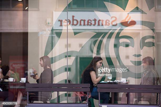 Customers sit and eat sandwiches and drink beverages inside a Starbucks Corp. Coffee shop in London, U.K., on Monday, June 9, 2014. U.K. Services...