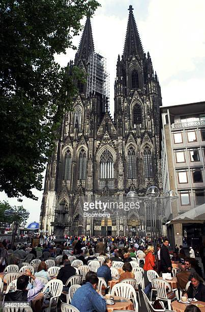 Customers sit at a cafe in front of the main cathedral in Cologne, Germany, Saturday, June 3, 2006.