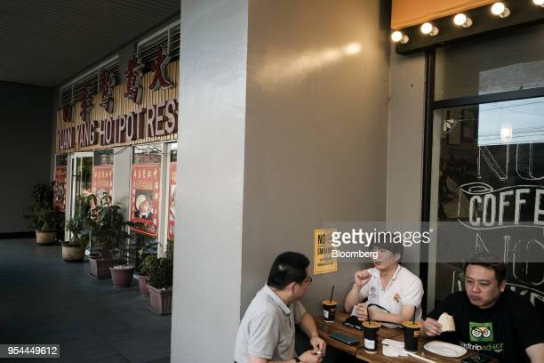 Customers sit at a coffee shop in the San Antonio Village area of Makati City Manila the Philippines on Wednesday May 2 2018 Home prices in the...