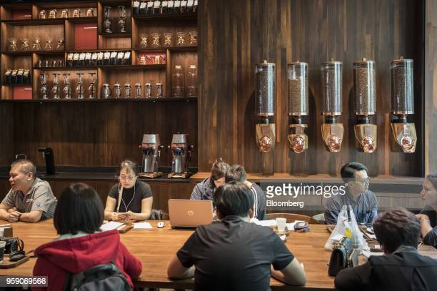 Customers sit at a communal table inside the Starbucks Corp Reserve Roastery store in Shanghai China on Friday May 11 2018 Starbucksis laying out an...