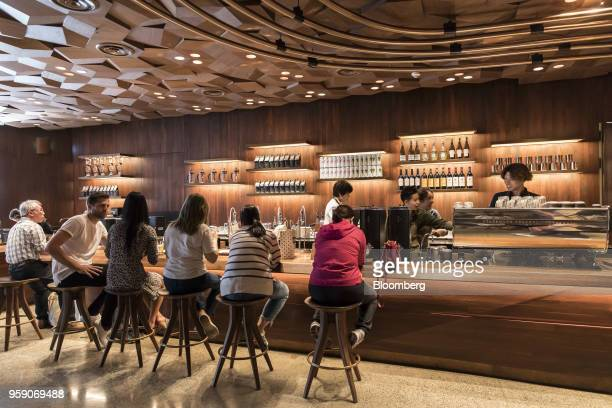 Customers sit at a counter inside the Starbucks Corp Reserve Roastery store in Shanghai China on Friday May 11 2018 Starbucksis laying out an...