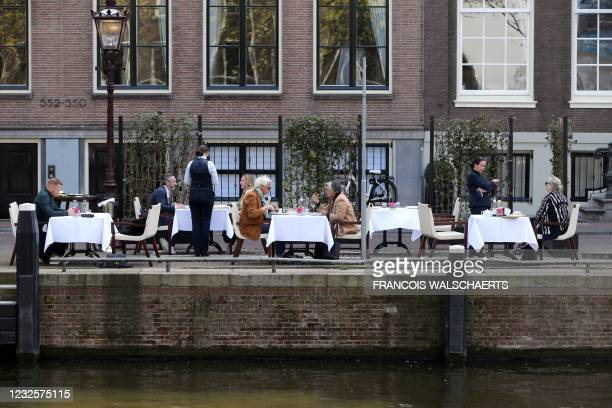 Customers sit at a restaurant's terrace alongside a canal in Amsterdam, on April 28 as the Dutch government eased the restrictions put in place to...