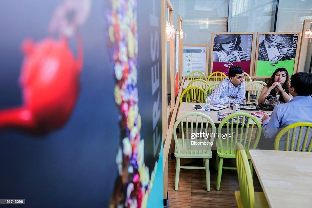Customers sit at a table inside a Tea Trails cafe, operated by Zone8 Tea World Pvt., in Mumbai, India, on Friday, Sept. 25, 2015. That sweet and milky tea concoction called chai is getting an image makeover in India. Rising incomes and demand for a refined experience transcending chai are spawning posh tea lounges in the nation's biggest cities. Photographer: Dhiraj Singh/Bloomberg via Getty Images