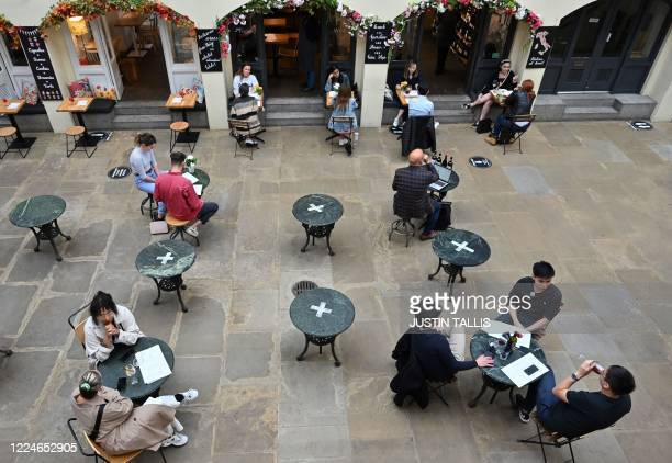 Customers sit at socially distanced tables in Covent Garden in London on July 4 as restrictions are further eased during the novel coronavirus...