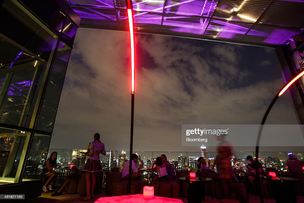 Customers sit at tables at the Park Society rooftop bar in the Sofitel So hotel, operated by Accor SA, at night in Bangkok, Thailand, on Saturday, June 28, 2014. Through a dozen coups, a tsunami, financial upheaval, floods and riots, Bangkok keeps bouncing back. With each crisis, tourism numbers slump, stocks crash and investment dips, only to return stronger than before. Photographer: Dario Pignatelli/Bloomberg via Getty Images