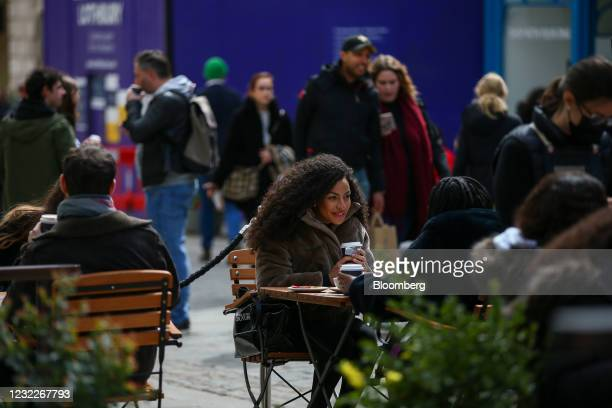 Customers sit at tables outside a cafe in Covent Garden in London, U.K., on Monday, April 12, 2021. Non-essential retailers as well as pubs and...